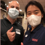 man and woman from UConn Athletic Training wearing masks and giving thumbs up